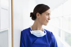 Young doctor in scrubs, smiling - stock photo