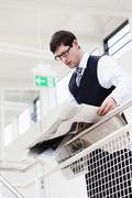 Germany, Bavaria, Diessen am Ammersee, Businesssman leaning on railing and - stock photo