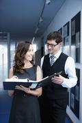 Stock Photo of Close up of businesspeople holding folder and discussing, smiling