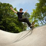 Germany, NRW, Duesseldorf, Man skateboarding at public skatepark - stock photo