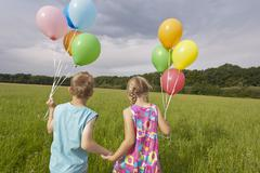 Stock Photo of Girl and boy holding balloons and walking in meadow
