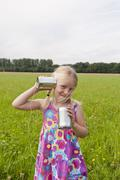 Stock Photo of Girl standing in meadow and playing with tin can phone