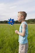 Germany, North Rhine-Westphalia, Hennef, Boy blowing wind mill in meadow - stock photo