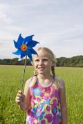 Germany, North Rhine-Westphalia, Hennef, Girl standing with wind mill in meadow Stock Photos