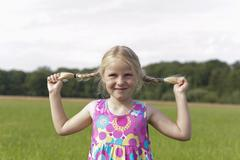 Germany, North Rhine-Westphalia, Hennef, Girl holding her braids in meadow, - stock photo