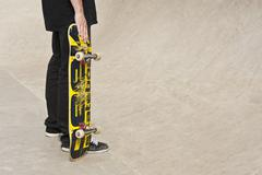 Germany, Duesseldorf, Man holding skateboard in public skate park - stock photo