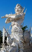 sculpture soldier guards the entrance to the white temple in chiang mai. - stock photo