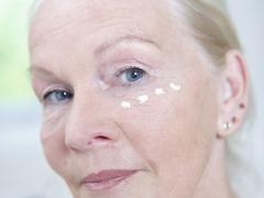Senior woman with face cream on face, portrait - stock photo
