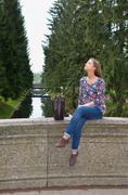 eautiful girl sits on an old stone bridge - stock photo