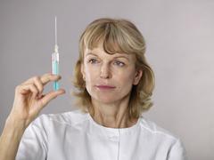 Mature female doctor examining syringe Stock Photos