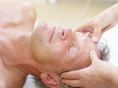 Stock Photo of Mature man recieving head massage, close up