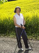 Germany, Mature woman nordic walking, smiling, portrait Stock Photos