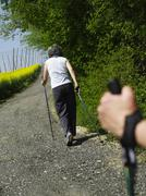 Germany, Bavaria, Mature woman nordic walking with man holding pole - stock photo