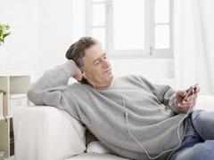 Stock Photo of Germany, Hamburg, Senior man listening MP3 player