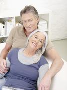 Stock Photo of Germany, Hamburg, Senior couple resting on sofa, smiling, portrait