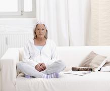 Stock Photo of Germany, Hamburg, Senior woman sitting on sofa, portrait