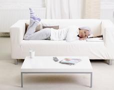Stock Photo of Germany, Hamburg, Senior woman lying on sofa with magazine