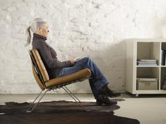 Stock Photo of Germany, Hamburg, Senior woman sitting on chair and listening music