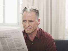 Stock Photo of Germany, Hamburg, Senior man reading newspaper