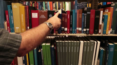 Man in library replace books on shelf genealogy HD 8748 Stock Footage