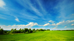 Summer green field landscape with clouds running across the sky, time-lapse. - stock footage
