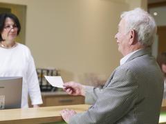 Germany, Hamburg, Senior man giving cheque to woman, smiling Stock Photos