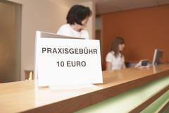 Stock Photo of Germany, Hamburg, Women standing with text board in foreground at clinic