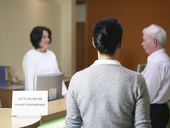 Germany, Hamburg, People standing near desk  in clinic - stock photo