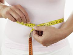 Stock Photo of Mid adult woman measuring her waist, close up