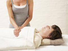 Woman receiving reiki treatment from masseur Stock Photos
