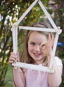 Close up of girl holding house shape made up of folding ruler, smiling, portrait - stock photo