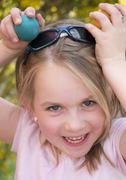 Germany, Bavaria, Close up of girl joking with easter eggs, smiling, portrait Stock Photos