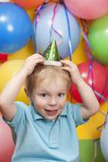 Boy wearing party hat with balloons in background, smiling, portrait - stock photo