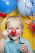 Boy at party with clown's nose and balloons in background, smiling, portrait - stock photo