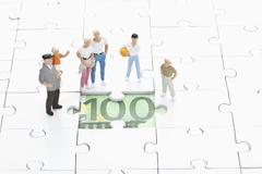 Figurine standing on jigsaw piece and watching 100 euro note - stock photo