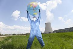 Germany, Bavaria, Man in protective workwear holding globe at AKW Isar Stock Photos