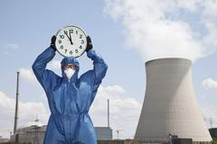 Germany, Bavaria, Unterahrain, Man in protective workwear holding clock at AKW Stock Photos