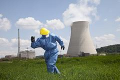 Germany, Bavaria, Unterahrain, Man with protective workwear running in field at Stock Photos