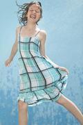 Saksa, tyttö hyppää tilkka vettä vasten sinistä taustaa Kuvituskuvat