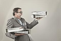 Close up of mature businessman at office holding stack of file - stock photo