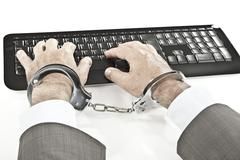 Close up of businessman's hand cuffed while cyber crime - stock photo