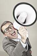 Close up of businessman screaming through megaphone against grey background Stock Photos