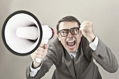 Close up of businessman screaming through megaphone against grey background - stock photo