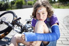 Germany, Bavaria, Wounded girl sitting on road after bicycle accident Stock Photos