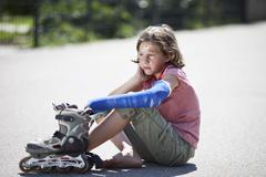 Germany, Bavaria, Wounded girl sitting on road after inline-skating accident Stock Photos