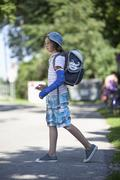 Germany, Bavaria, Wounded girl with arm in cast on way to school - stock photo