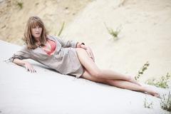 Germany, Bavaria, Young woman in beachwear lying on beach, portrait - stock photo