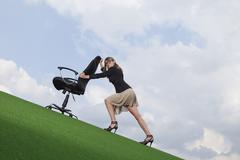 Stock Photo of Germany, Bavaria, Munich, Businesswoman pushing chair on lawn