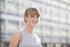 Germany, Bavaria, Munich, Young businesswoman smiling and looking away - stock photo