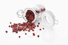 Stock Photo of Dry red pepper in glass jar spilling on white background